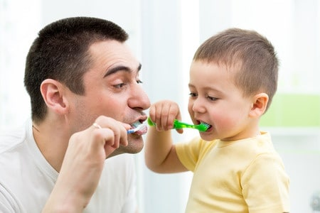 Dad and son brushing teeth